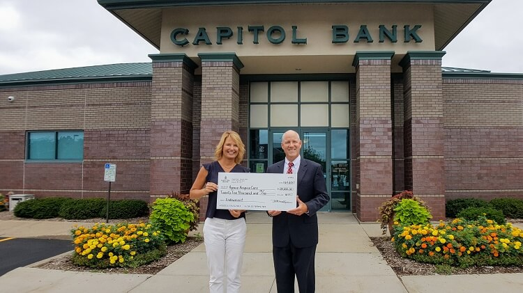 $25,000 check being given to Agreace Hospice Care outside of Capitol Bank Madison