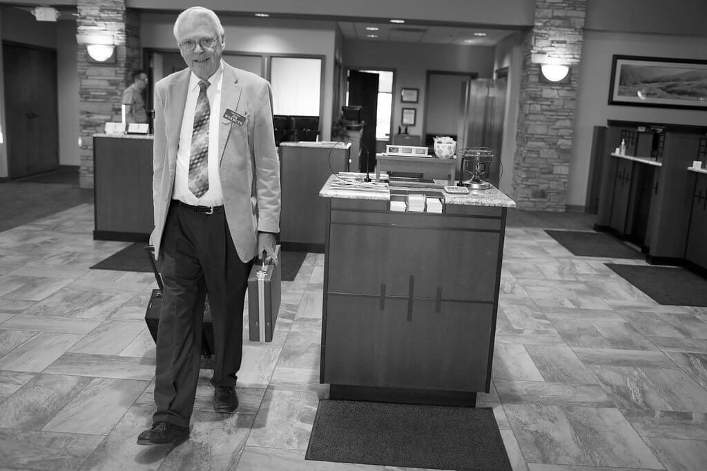 Jim Wermuth Leaving the bank with a briefcase and roller suitcase